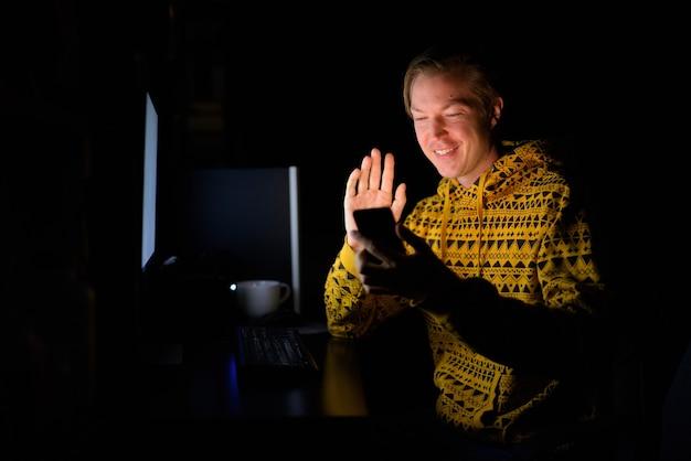 Homem bonito jovem feliz fazendo videochamadas com telefone enquanto trabalhava horas extras em casa no escuro
