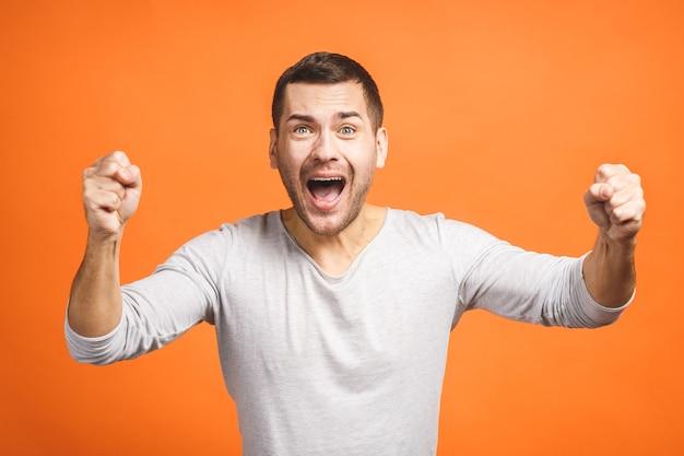 Homem bonito jovem feliz gesticulando e mantendo a boca aberta