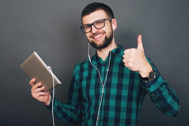 Homem bonito jovem hippie em fundo cinza segurando um tablet, ouvindo música em fones de ouvido, falando on-line, óculos de camisa quadriculada verde sorridente feliz, humor positivo
