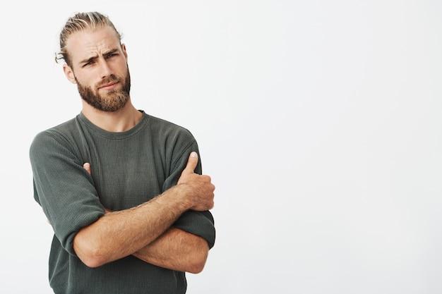 Homem bonito jovem hippie posando com braços cruzados