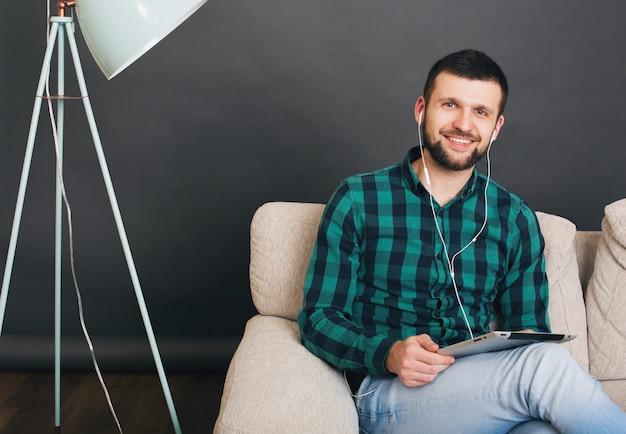 Homem bonito jovem hippie sentado no sofá em casa segurando o tablet, ouvindo música em fones de ouvido, falando online, feliz, sorridente, camisa quadriculada verde, lazer, descansando