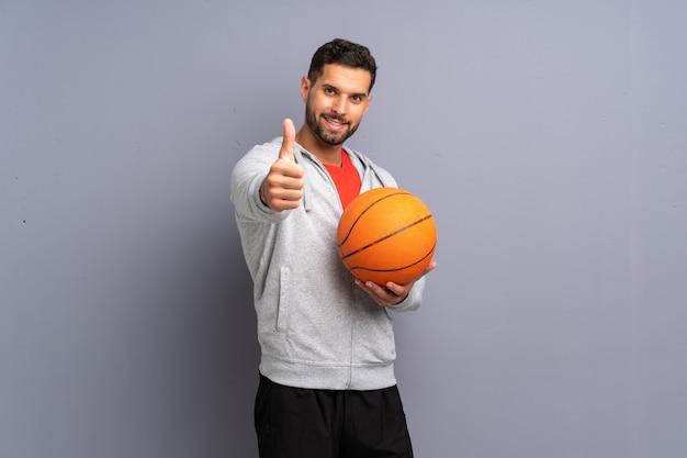 Homem bonito jovem jogador de basquete com polegares para cima porque algo bom aconteceu