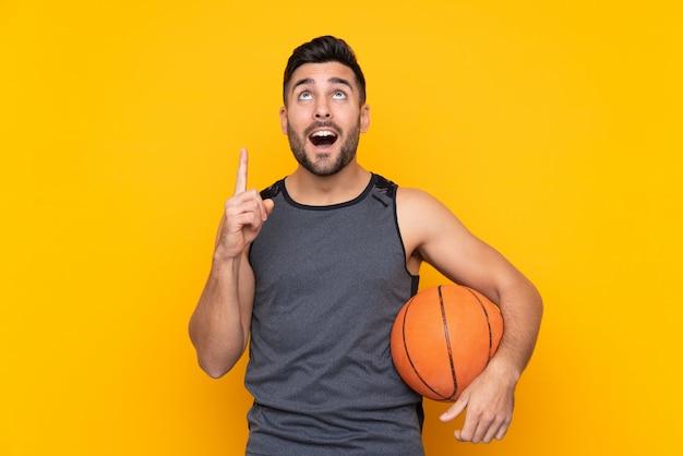 Homem bonito jovem jogador de basquete sobre parede branca isolada, apontando para cima uma ótima idéia