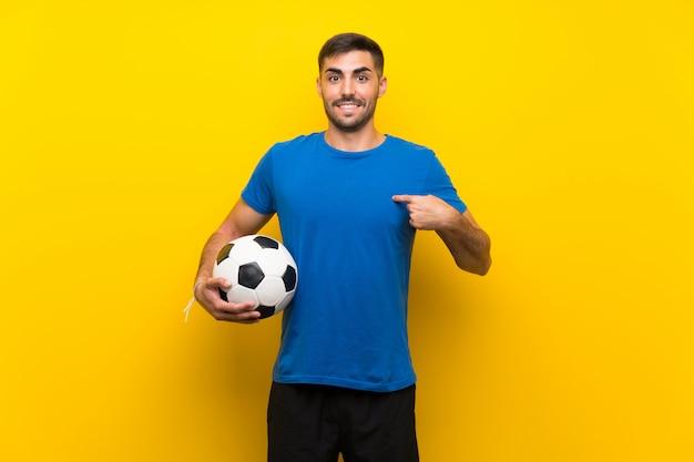 Homem bonito jovem jogador de futebol isolado parede amarela com expressão facial de surpresa