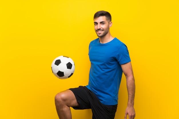 Homem bonito jovem jogador de futebol isolado parede amarela