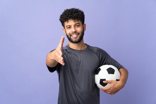 Homem bonito jovem jogador de futebol marroquino isolado na parede roxa apertando as mãos para fechar um bom negócio