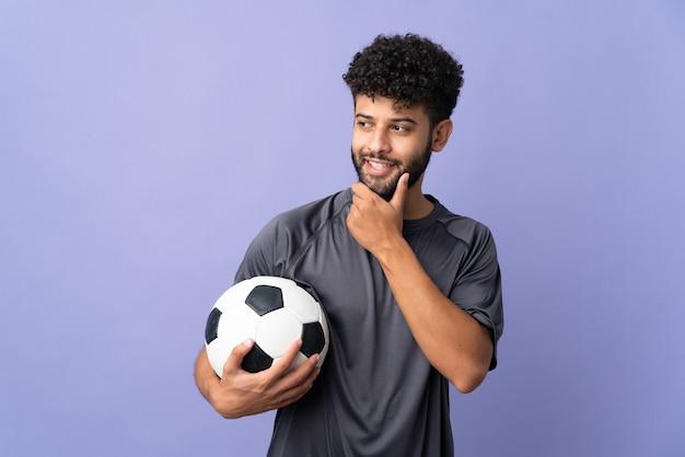 Homem bonito jovem jogador de futebol marroquino isolado na parede roxa, olhando para o lado e sorrindo