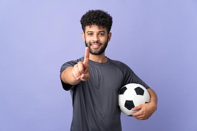 Homem bonito jovem jogador de futebol marroquino isolado no fundo roxo, mostrando e levantando um dedo