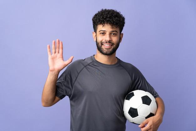 Homem bonito jovem jogador de futebol marroquino isolado no roxo, saudando com a mão com uma expressão feliz