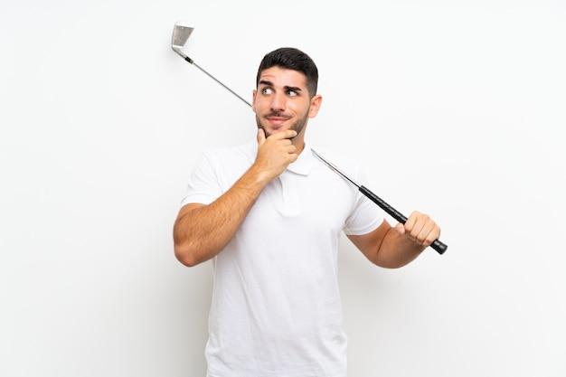 Homem bonito jovem jogador de golfe sobre branco isolado pensando uma idéia