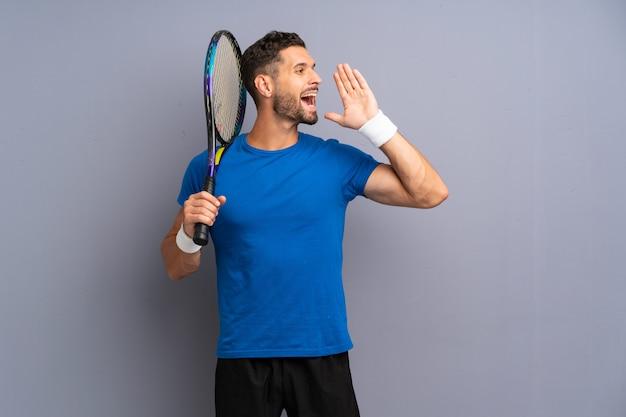 Homem bonito jovem jogador de tênis, gritando com a boca aberta