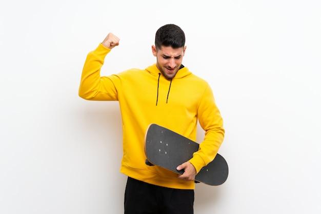 Homem bonito jovem patinadora na parede branca, celebrando uma vitória