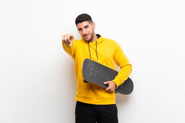 Homem bonito jovem patinadora na parede branca