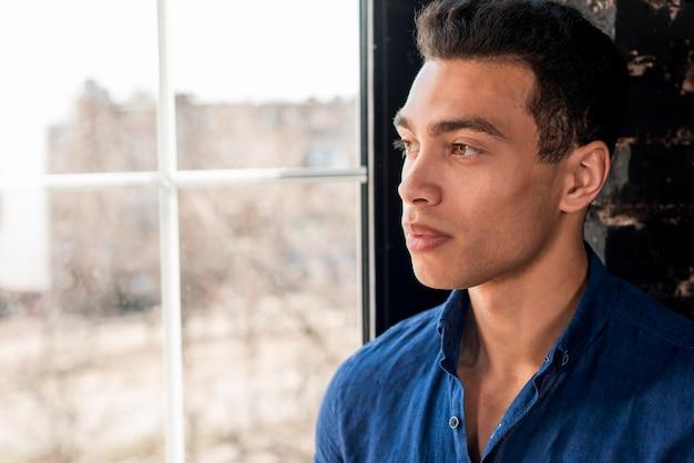 Homem bonito jovem pensativo olhando pela janela