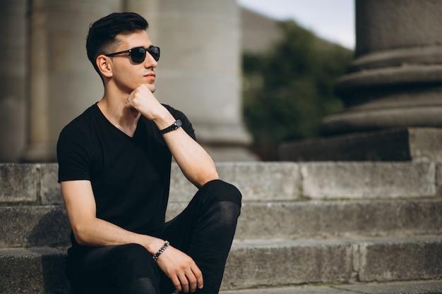 Homem bonito jovem sentado na escada