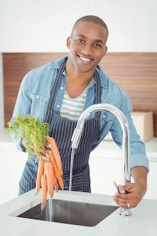 Homem bonito lavar as cenouras na cozinha
