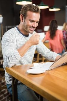 Homem bonito, lendo jornal e tomando um café