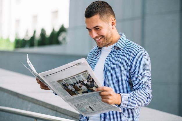 Homem bonito lendo jornal na rua