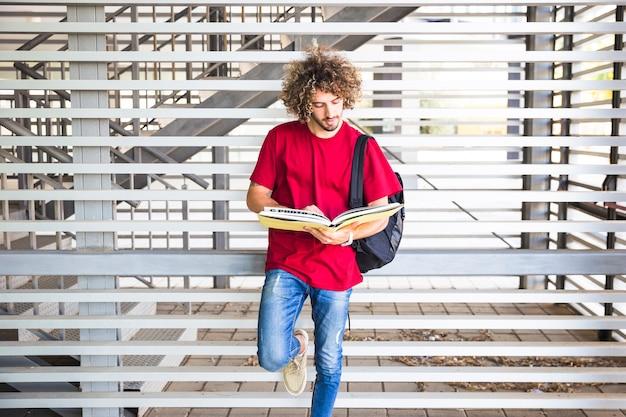 Homem bonito lendo livro perto da parede
