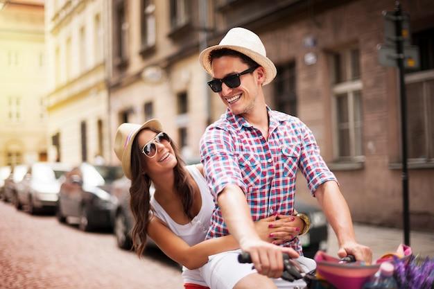 Homem bonito levando a namorada no suporte para bicicletas