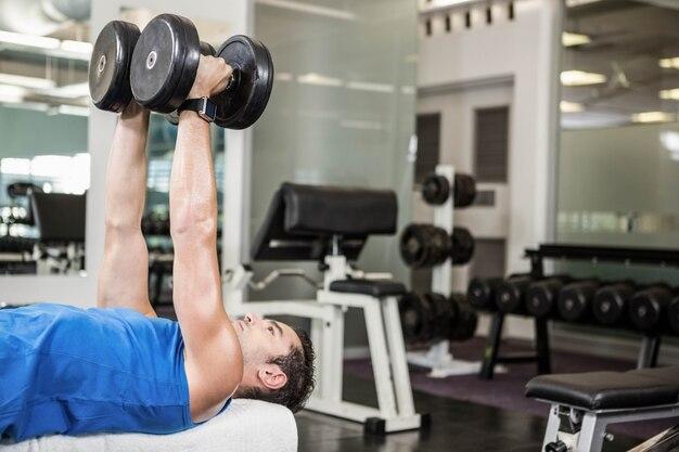 Homem bonito levantando halteres no banco no ginásio