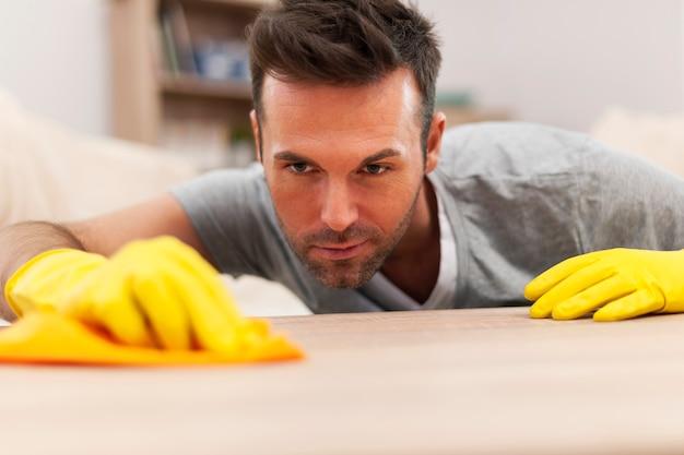 Homem bonito limpando manchas da mesa