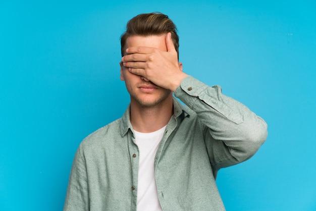 Homem bonito loiro com camisa verde, cobrindo os olhos pelas mãos