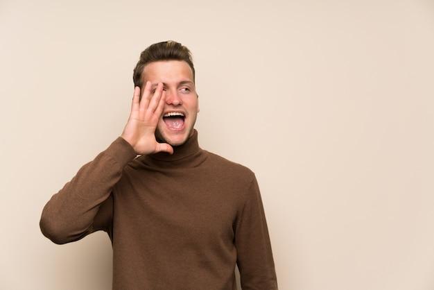 Homem bonito loiro sobre parede isolada gritando com a boca aberta