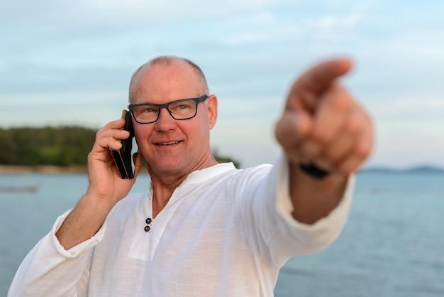 Homem bonito maduro e feliz turista apontando o dedo e usando o telefone contra a vista da praia ao ar livre