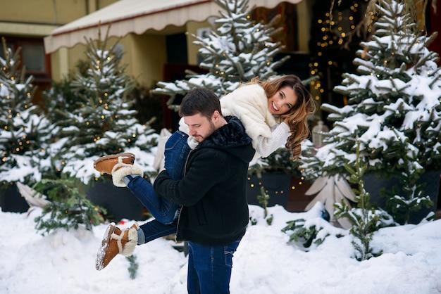 Homem bonito mantém sua linda namorada sorridente no ombro na árvore de natal com luzes. férias de inverno, natal e ano novo.