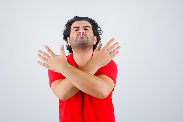 Homem bonito, mantendo o cigarro na boca, segurando os dois braços cruzados, gesticulando o sinal x na camiseta vermelha e olhando com raiva, vista frontal.
