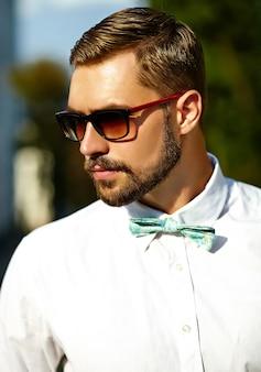Homem bonito modelo hipster em roupas de verão elegante posando em óculos de sol