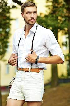 Homem bonito modelo hipster em roupas de verão elegante posando