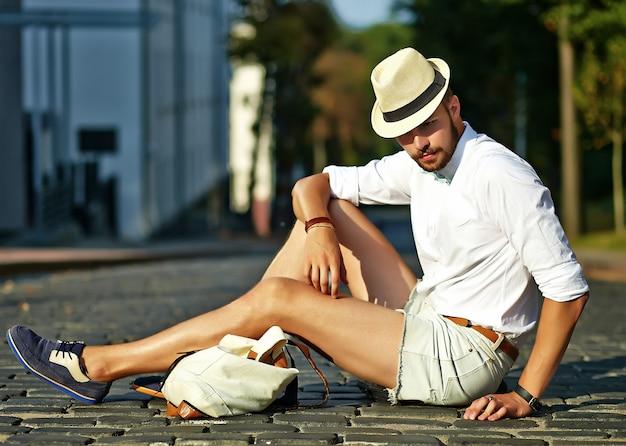 Homem bonito modelo hipster em roupas de verão elegante, sentado no chapéu com bolsa