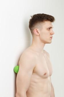 Homem bonito mostra exercícios usando a bola com espinhos