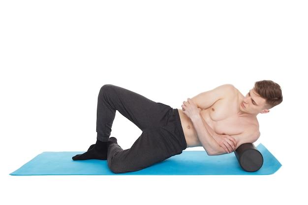 Homem bonito mostra exercícios, usando um rolo de espuma para uma massagem de liberação miofascial no colchonete em estúdio. isolado no branco