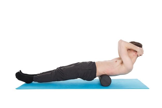 Homem bonito mostra exercícios usando um rolo de espuma