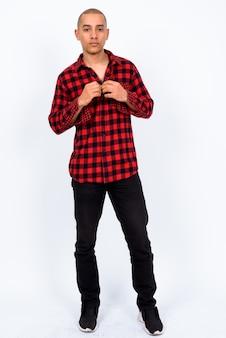 Homem bonito, multiétnico, careca, moderno, vestindo uma camisa quadriculada vermelha contra uma parede branca