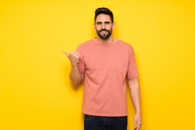 Homem bonito muro amarelo apontando para o lado para apresentar um produto