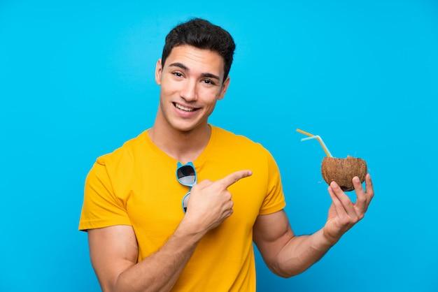Homem bonito muro azul com um coco