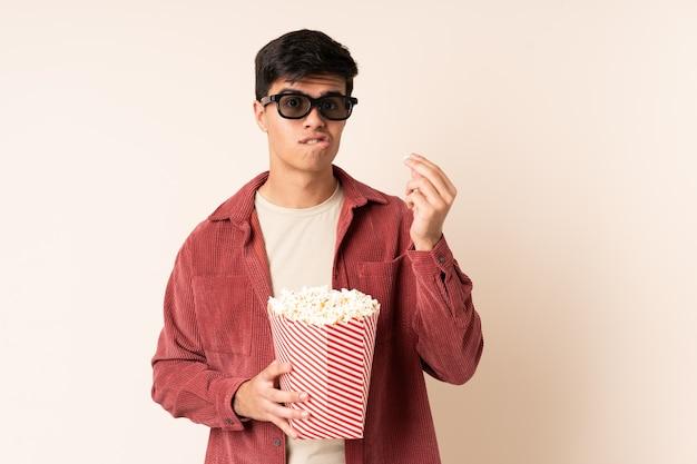 Homem bonito muro com óculos 3d e segurando um grande balde de pipocas