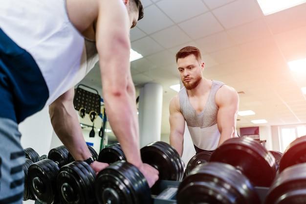 Homem bonito musculoso com halteres pesados em frente ao espelho no pavilhão desportivo. fisiculturista forte está tomando halteres pretos para treino na frente de um espelho.