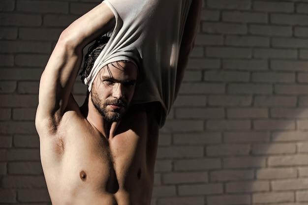 Homem bonito musculoso sem camisa depois do banho.