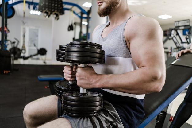 Homem bonito musculoso treinando com halteres pesados no ginásio. jovem com bíceps grande senta-se e faz exercícios dentro de casa. conceito de esporte e saúde.