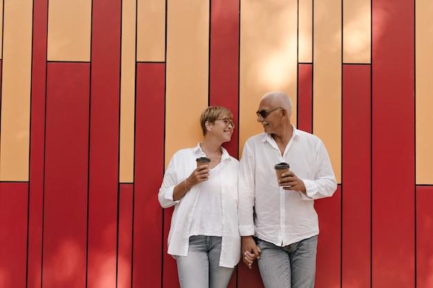Homem bonito na camisa branca, de mãos dadas com a senhora loira na blusa clara e óculos com uma xícara de chá em vermelho e laranja.