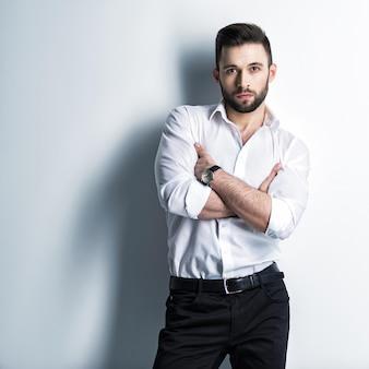 Homem bonito na camisa branca e calça preta - posando cara atraente com penteado da moda. homem confiante com barba curta. menino adulto elegante com cabelo castanho.
