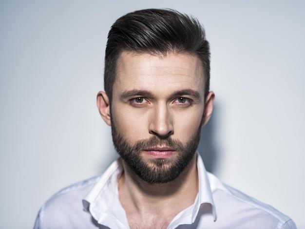 Homem bonito na camisa branca, posando. cara atraente com penteado da moda. homem confiante com barba curta. menino adulto com cabelo castanho. retrato do close up.