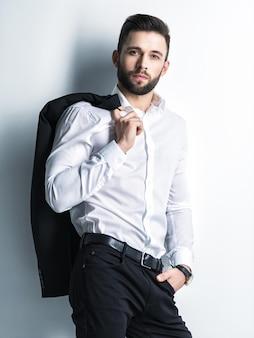Homem bonito na camisa branca segura o terno preto - posando sobre a parede. cara atraente com penteado da moda. homem confiante com barba curta. menino adulto com cabelo castanho. retrato completo.