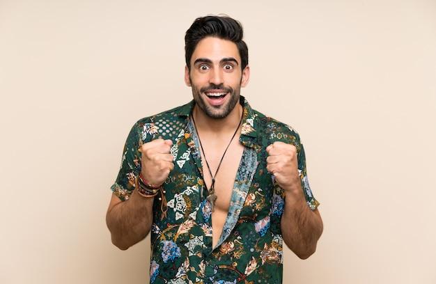 Homem bonito na camisa de verão sobre fundo isolado, celebrando uma vitória