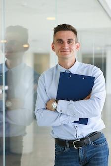 Homem bonito na camisa e pasta fica no escritório olhando na câmera as mãos cruzadas no peito. codemodern escritório estilo de vida pós-graduação faculdade estudo estudo idéia treinador conceito de trem